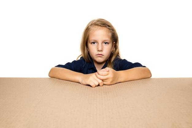 Śliczna i zdenerwowana mała dziewczynka otwierająca największe opakowanie. rozczarowana młoda modelka na tekturowym pudełku