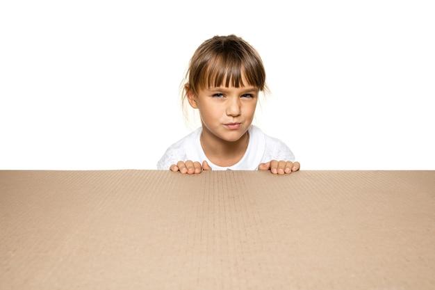 Śliczna i zdumiona mała dziewczynka na największej paczce pocztowej. podekscytowana młoda modelka na tekturowym pudełku patrząc do środka.