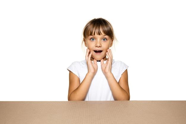 Śliczna i zdumiona mała dziewczynka otwierająca największą paczkę pocztową. podekscytowana młoda modelka na tekturowym pudełku
