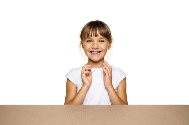 Śliczna i zdziwiona mała dziewczynka otwierająca największą paczkę pocztową.