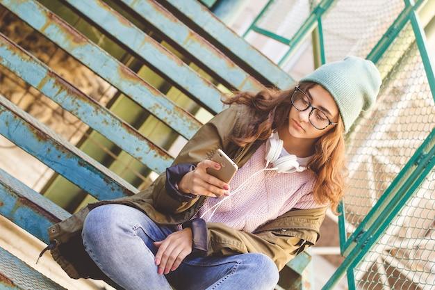 Śliczna indiańska nastoletnia dziewczyna używa smartphone. młoda kobieta pisze wiadomość na telefonie komórkowym.
