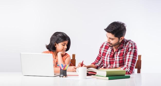 Śliczna indyjska dziewczyna z ojcem studiuje lub odrabia pracę domową w domu za pomocą laptopa i książek - koncepcja edukacji online