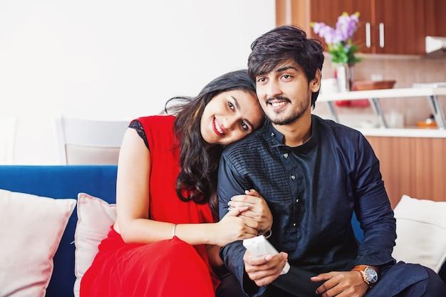 Śliczna indyjska para ogląda telewizję w domu podczas przytulania