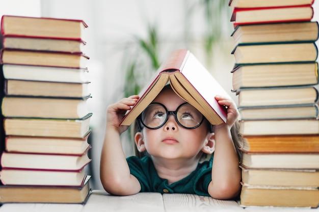 Śliczna inteligentna dziewczynka w wieku przedszkolnym czytająca książki w bibliotece lub w domu dzieci wczesne uczenie się edukacji domowej