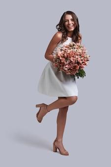 Śliczna jak kwiat. pełna długość atrakcyjnej młodej kobiety trzymającej bukiet kwiatów i uśmiechającej się, pozując na szarym tle