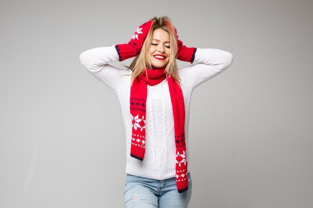 Śliczna jowialna dziewczyna w szaliku z dzianiny i rękawiczkach, czepiająca się we włosach z zębami uśmiechem i zamkniętymi oczami.
