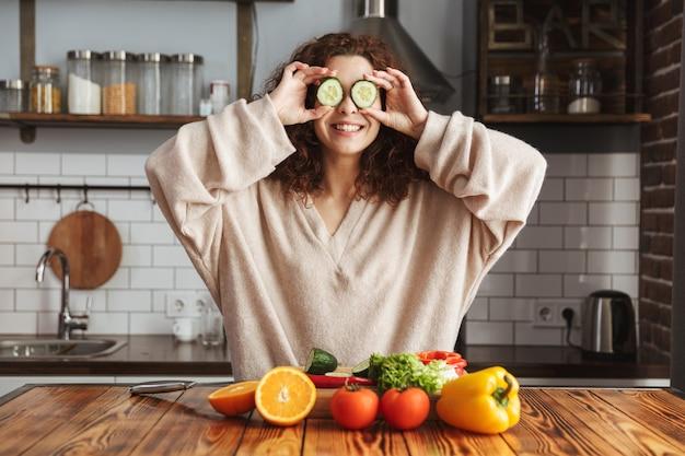 Śliczna kaukaska kobieta bawi się podczas gotowania sałatki ze świeżymi warzywami w kuchni w domu