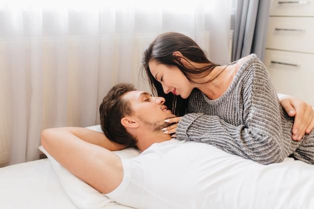 Śliczna kaukaska kobieta z eleganckim manicure spędza czas w łóżku przed pracą i uśmiecha się do męża