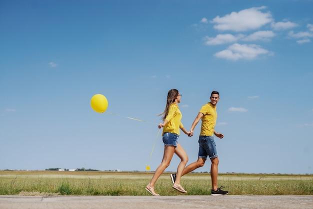 Śliczna kaukaska nastoletnia para ubierał w błękitnym i żółtym stroju trzyma ręki i biega outdoors z balonem.