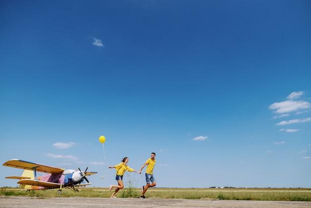 Śliczna kaukaska nastoletnia para ubierał w błękitnym i żółtym stroju trzyma ręki i biega outdoors