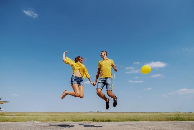 Śliczna kaukaska nastoletnia para ubierał w błękitnym i żółtym stroju trzyma ręki i skacze outdoors z balonem.