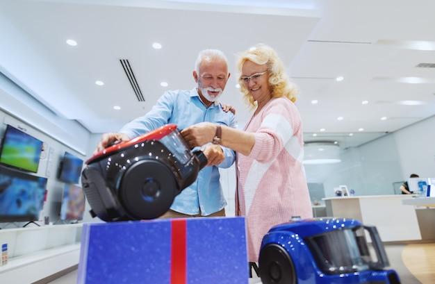 Śliczna kaukaska starsza para wybiera nowego odkurzacz dla ich domu. wnętrze sklepu technicznego.