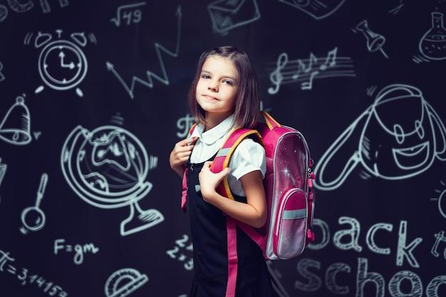 Śliczna kaukaska uczennica przygotowuje się do pójścia do szkoły z plecakiem z powrotem do koncepcji szkoły
