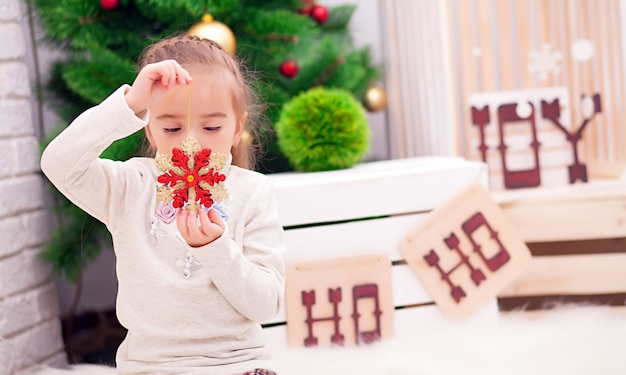 Śliczna kędzierzawa berbeć dziewczyna stoi przy bożenarodzeniowym obiadowym stołem załatwia naczynia przygotowywać świętować xmas eve, widok przez okno od outside w dekorującą jadalnię z drzewem i światłami