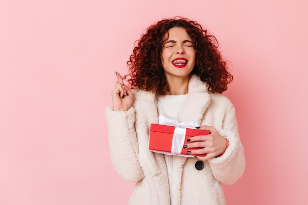 Śliczna kędzierzawa dama zamknęła oczy i skrzyżowała palce. portret kobiety w białym fartuchu, trzymając czerwone pudełko na różowej przestrzeni.