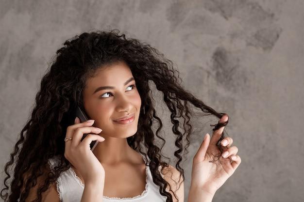 Śliczna kędzierzawa kobieta opowiada na telefonie, stacza się włosianego pasemko na palcu
