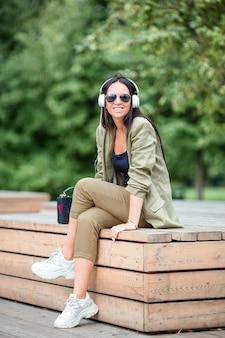 Śliczna kobieta czyta wiadomość tekstową na telefonie komórkowym podczas gdy siedzący w parku.