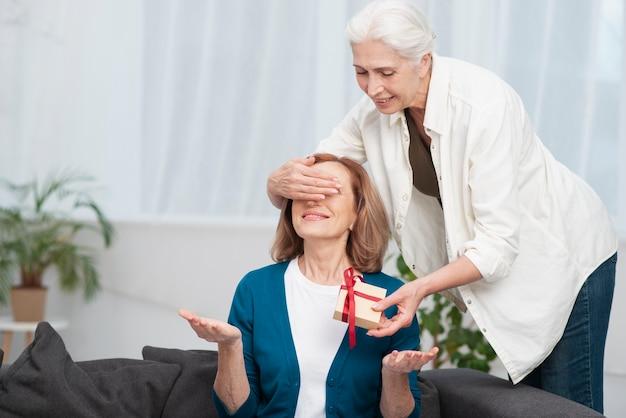 Śliczna kobieta daje jej przyjacielowi prezentowi
