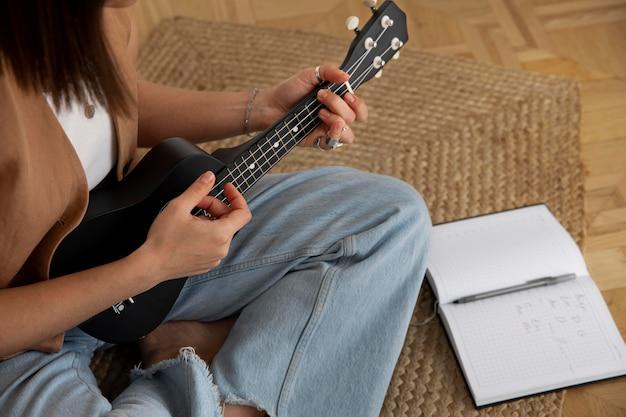 Śliczna kobieta grająca na ukulele w domu