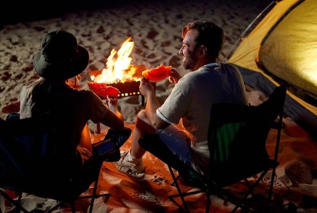 Śliczna kobieta i przystojny mężczyzna siedzą na składanych krzesełkach w pobliżu namiotu przy ognisku, jedzą arbuza i bawią się nocą na plaży nad morzem.