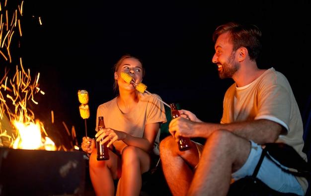 Śliczna kobieta i przystojny mężczyzna siedzą na składanych krzesełkach w pobliżu namiotu przy ognisku, piją piwo, jedzą kukurydzę i bawią się nocą na plaży nad morzem.