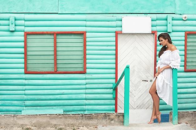 Śliczna kobieta jest ubranym piękną biel suknię pozuje blisko kolorowego drewnianego domu