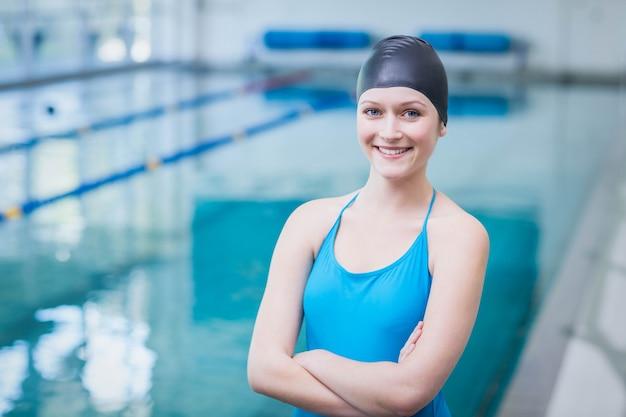 Śliczna kobieta jest ubranym pływanie nakrętkę z rękami krzyżować przy basenem