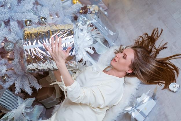 Śliczna kobieta leży na podłodze z prezentem w ręku przy choince wesołych i radosnych świąt ...