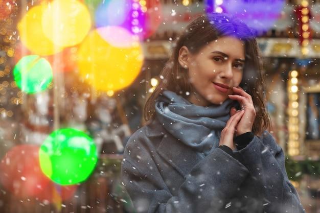 Śliczna kobieta nosi szary płaszcz spacerując po ulicy z bokeh podczas opadów śniegu. pusta przestrzeń