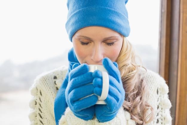 Śliczna kobieta pije kawę w ciepłej odzieży