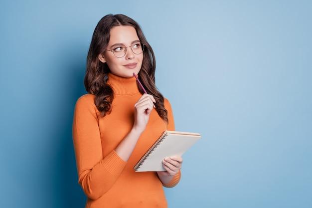 Śliczna kobieta pisze notatki w notatniku długopis podbródek wygląda koncepcja kreatywnego myślenia copyspace