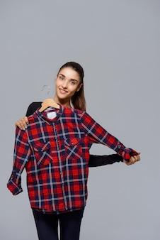 Śliczna kobieta podnosi strój, wybiera koszula