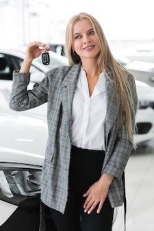 Śliczna kobieta pokazuje przy kluczami samochód i patrzeje daleko od