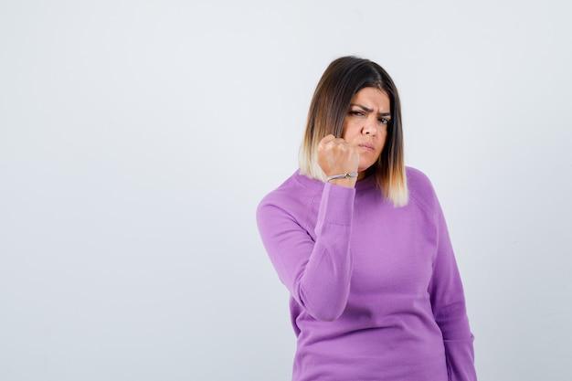 Śliczna kobieta pokazuje zaciśniętą pięść w fioletowym swetrze i wygląda na złośliwą. przedni widok.