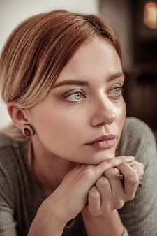 Śliczna kobieta. portret pięknej młodej kobiety niebieskooki na sobie stylową biżuterię i szarą sukienkę