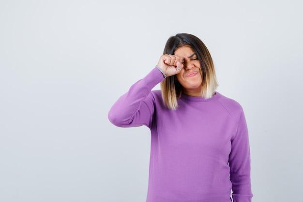 Śliczna kobieta przeciera oko, płacząc w fioletowym swetrze i patrząc żałobnie. przedni widok.