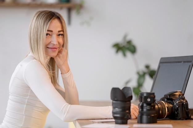 Śliczna kobieta przy jej workspace i kamera obiektywem