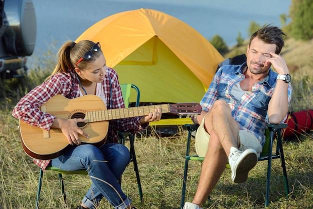Śliczna kobieta serenading jej mężczyzna na campingowej wycieczce.