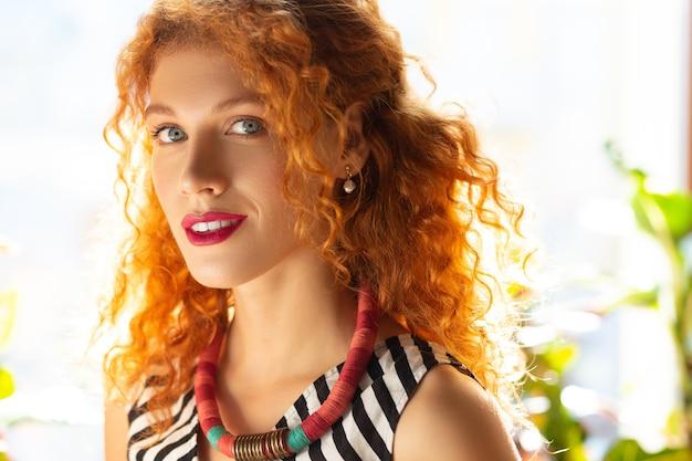 Śliczna kobieta. stylowa piękna rudowłosa kobieta w naszyjniku stojąca przy oknie
