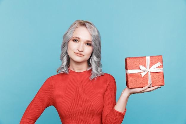 Śliczna kobieta trzyma czerwone pudełko na niebieskim tle