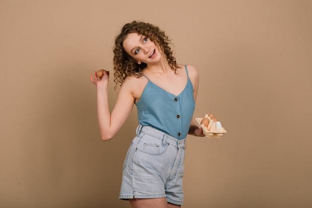 Śliczna kobieta trzyma jajka - kopia przestrzeń na szarej ścianie. portret emocjonalny