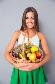 Śliczna kobieta trzyma kosz z owocami