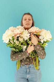 Śliczna kobieta trzyma pięknych kwiaty
