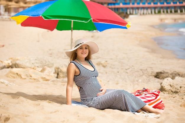Śliczna kobieta w ciąży ubrana w długą pasiastą sukienkę leżącą na piaszczystej plaży