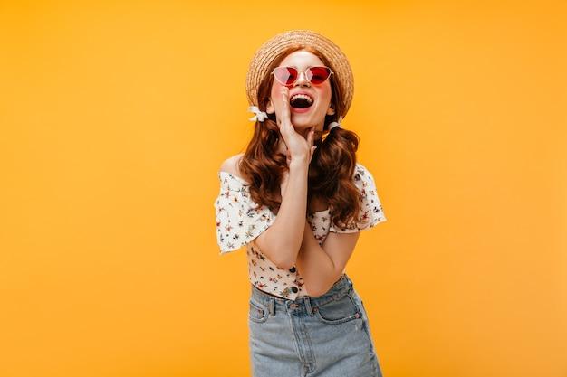 Śliczna kobieta w czerwonych okularach przeciwsłonecznych i krzyczy kapelusz. dama ubrana w dżinsową spódnicę, białą koszulkę i kapelusz pozuje na pomarańczowym tle.