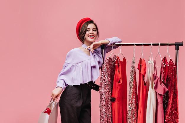 Śliczna kobieta w jasnym kapeluszu i fioletowej bluzce opiera się na stojaku z sukienkami i pozuje z paczką na na białym tle.