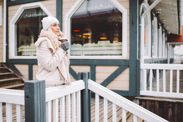 Śliczna kobieta w średnim wieku cieszyć się czasem na świeżym powietrzu w zimowy dzień. kobieta ubrana w lekką kurtkę, czapkę, szalik i pić gorący napój.