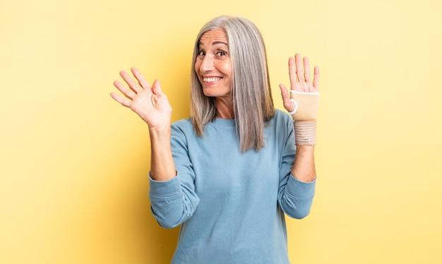 Śliczna kobieta w średnim wieku, uśmiechnięta radośnie, machająca ręką, witająca i pozdrawiająca. koncepcja bandaża ręcznego