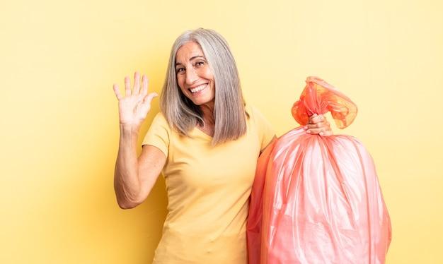 Śliczna kobieta w średnim wieku, uśmiechnięta radośnie, machająca ręką, witająca i pozdrawiająca. plastikowa torba garbaje