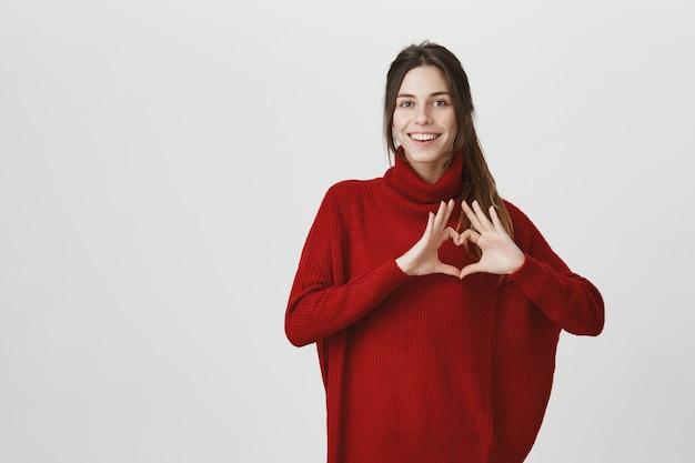 Śliczna kobieta w swetrze pokazuje znak serca i uśmiecha się